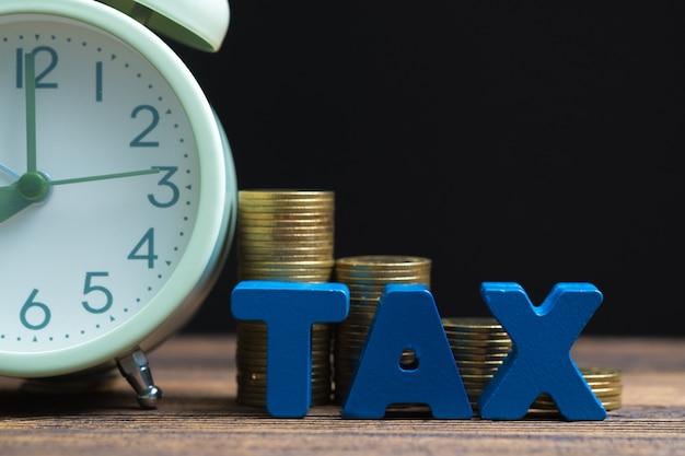Alfabeto fiscal com pilha de moeda e despertador vintage em madeira Foto Premium
