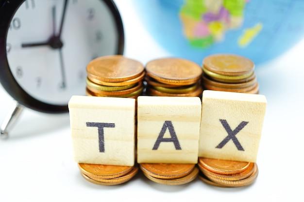 Alfabeto fiscal com pilha de moedas e despertador: tempo para pagar. Foto Premium