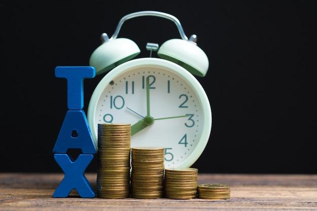 Alfabeto fiscal com pilha de moedas e despertador vintage Foto Premium