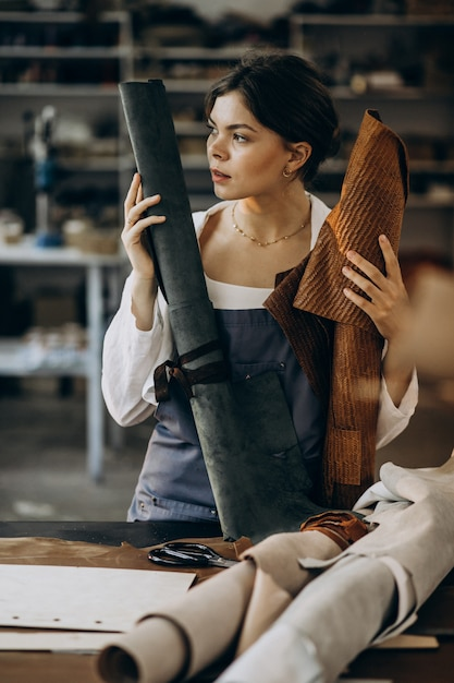 Alfaiate de mulher trabalhando em tecido de couro Foto gratuita