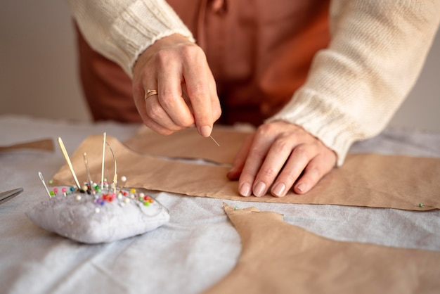Alfaiate mulher usando agulha e linha para costurar Foto gratuita