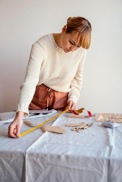 Alfaiate mulher usando régua para medir o tecido Foto gratuita