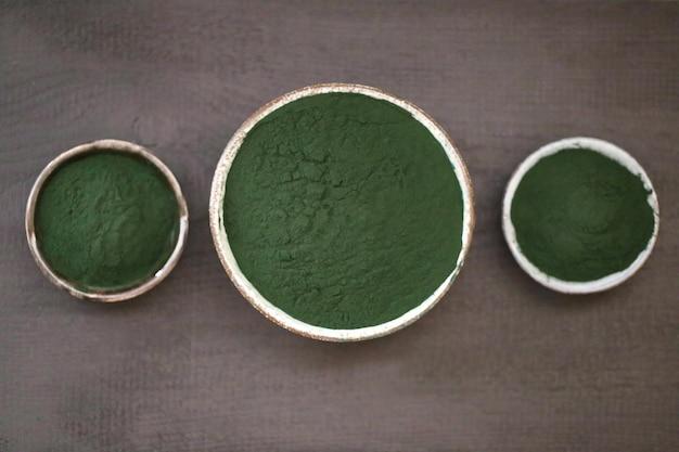 Algas spirulina. pó seco em copos redondos em uma mesa preta. Foto Premium