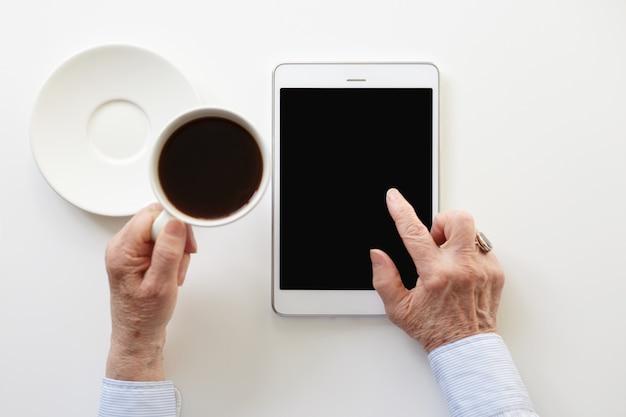Alguém está usando o touchpad enquanto toma uma xícara de café Foto gratuita