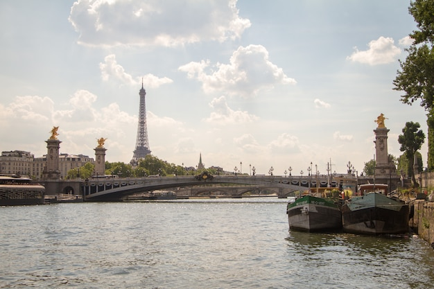 Algumas barcaças e alexander the third bridge no fundo da torre eiffel em paris Foto Premium