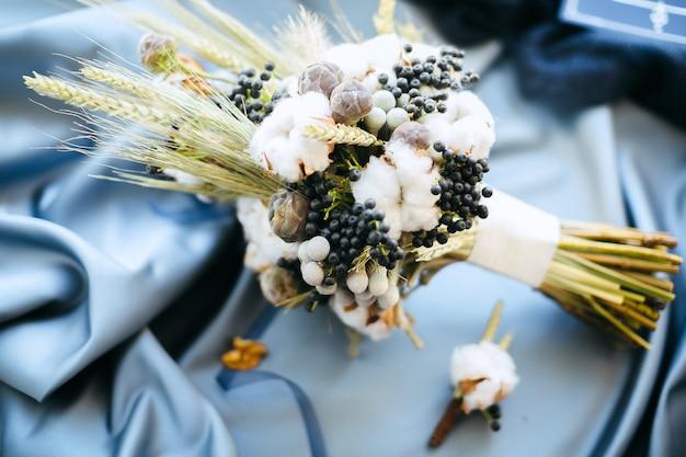Algumas decorações de casamento, flores sobre fundo azul de pano, vista de alto ângulo. Foto gratuita