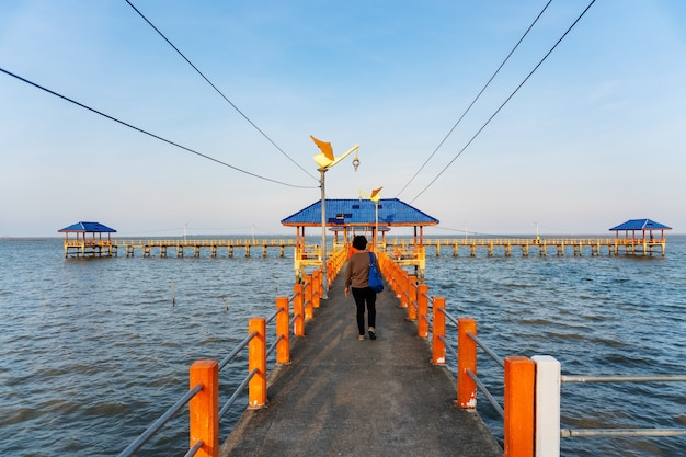 Algumas pessoas andando na ponte no mar azul Foto Premium