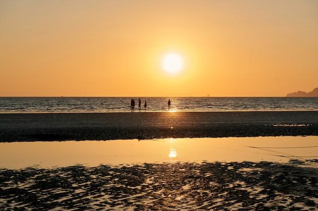 Algumas pessoas estão na praia durante o pôr do sol Foto Premium