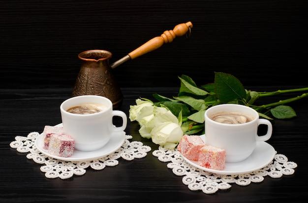 Algumas xícaras de café com leite, cezve, doces orientais, um buquê de rosas brancas Foto Premium