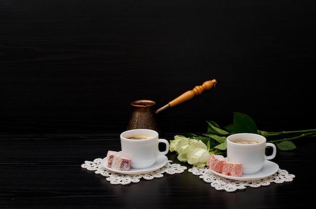 Algumas xícaras de café com leite, cezve, turkish delight, um buquê de rosas brancas. espaço para texto Foto Premium