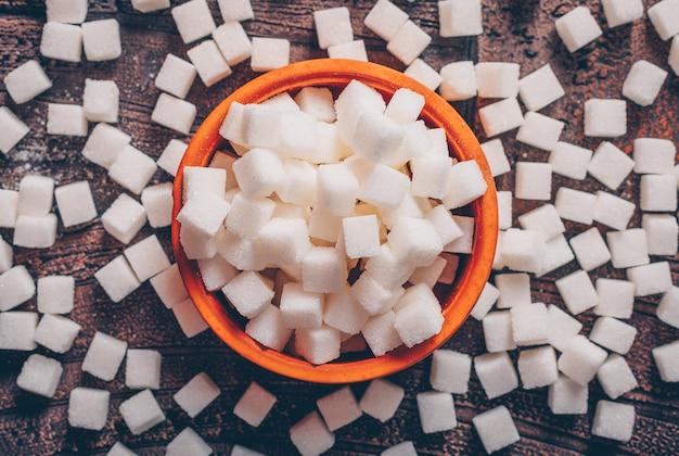 Alguns cubos de açúcar branco em uma tigela laranja na mesa de madeira escura, plana leigos. Foto gratuita