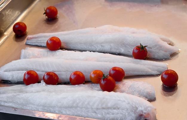 Alguns pedaços de bacalhau cru e tomate Foto Premium