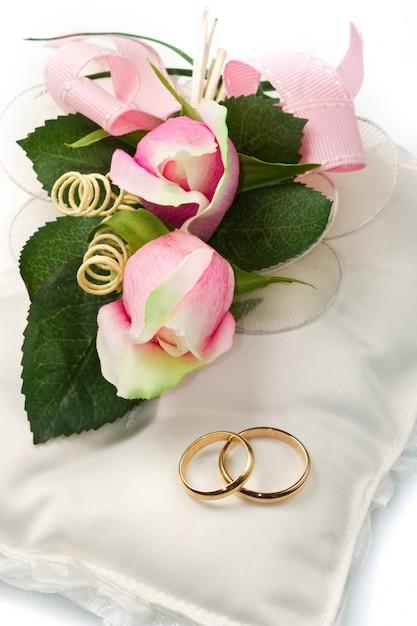 Alianças de casamento de ouro no travesseiro branco com rosa Foto Premium