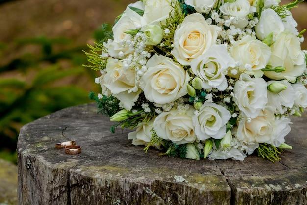 Alianças de casamento e buquê de noiva no coto, o buquê de noiva Foto Premium