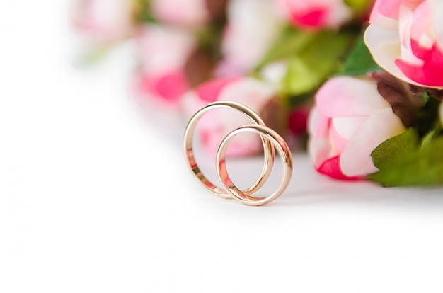 Alianças de casamento e flores isoladas em branco Foto Premium