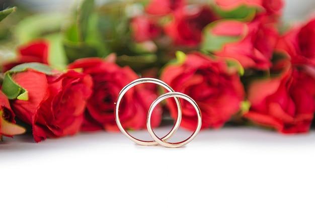 Alianças de casamento e flores isoladas no fundo branco Foto Premium