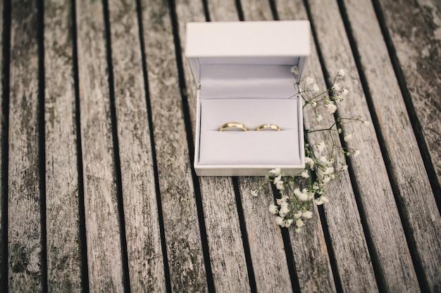 Alianças de casamento em uma caixa em cima da mesa. pequenas flores em uma mesa de madeira Foto Premium