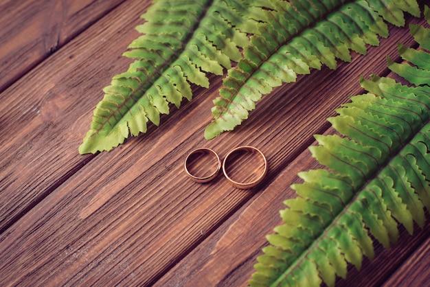 Alianças de casamento embrulhadas em um fundo de madeira com folhas Foto Premium
