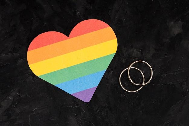 Alianças de casamento multicoloridas e coração lgbt em fundo preto Foto gratuita