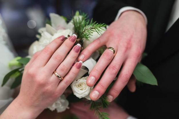 Alianças de casamento nas mãos dos recém-casados. Foto Premium