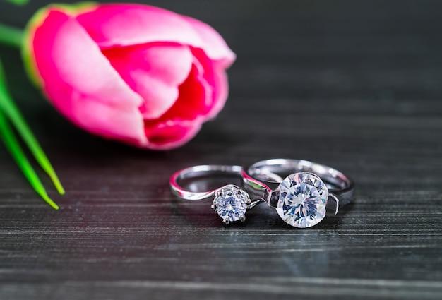 Alianças de diamante com flor tulipa em fundo preto Foto Premium