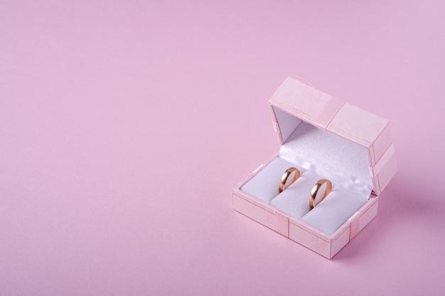 Alianças de ouro em caixa de presente rosa sobre fundo rosa suave, vista de ângulo, copie o espaço Foto Premium