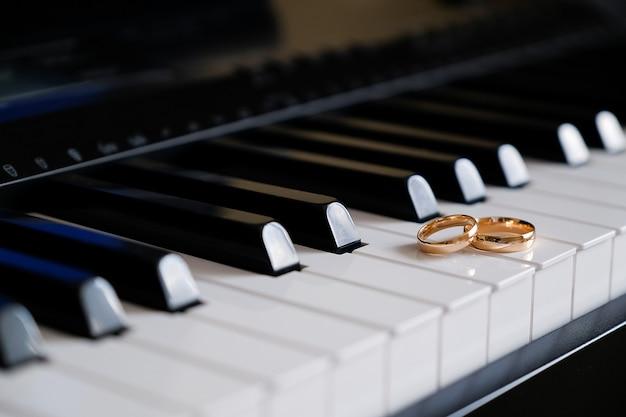 Alianças de ouro nas teclas do piano. Foto Premium