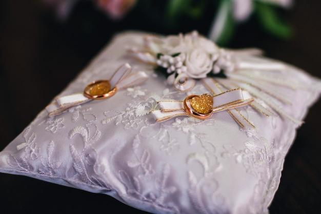 Alianças de ouro no travesseiro bonito branco Foto Premium
