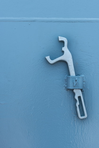 Alicates de metal prata no fundo da parede. os alicates penduram na parede branca. Foto Premium