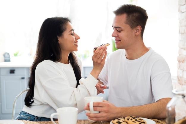 Alimentação feminina étnica com namorado cookie Foto gratuita