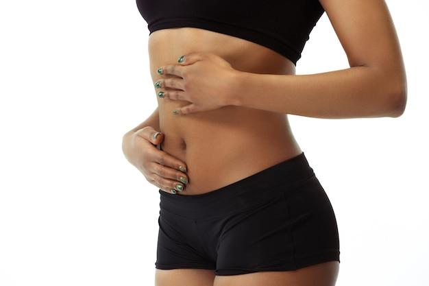 Alimentação, nutrição, dor de estômago. barriga magro de mulher bronzeada na parede branca. modelo afro-americano com forma e pele bem cuidadas. beleza, autocuidado, perda de peso, fitness, conceito de emagrecimento. Foto gratuita