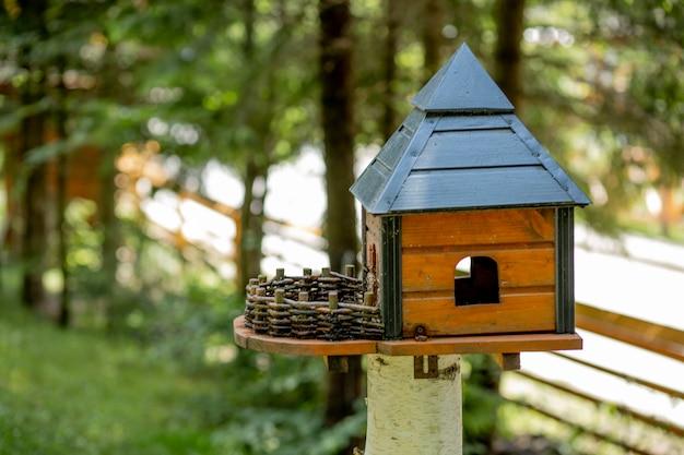 Alimentador de pássaros de madeira em forma de uma casa com telhado, anexado a um poste de madeira em uma floresta entre árvores na natureza Foto Premium