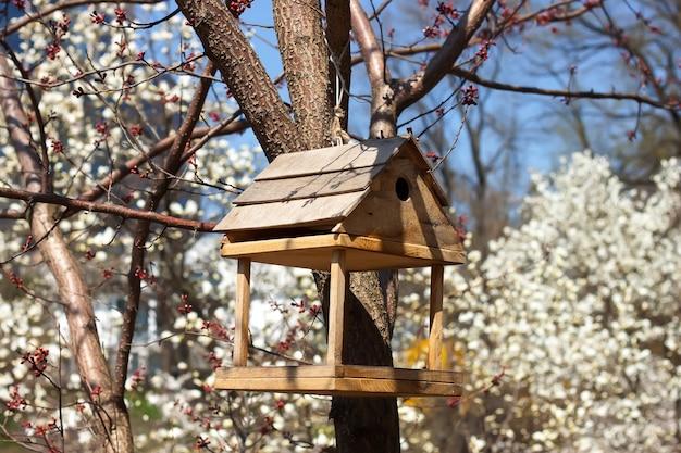 Alimentador para pássaros no jardim florido da primavera Foto Premium