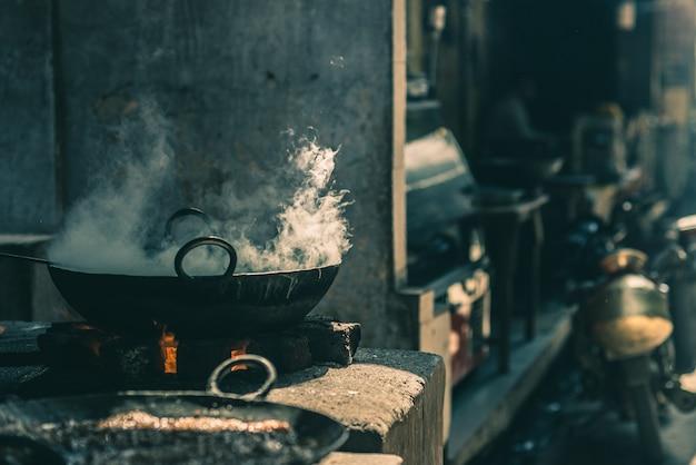 Alimento da rua na índia que cozinha na bandeja ou em wok grande fatiscent em uma tenda pequena do alimento da rua. Foto Premium