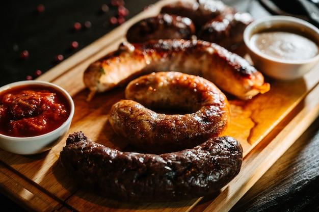 Alimento de oktoberfest, salsichas apetitosas da carne ,. uma grande variedade em uma bandeja de madeira. Foto Premium