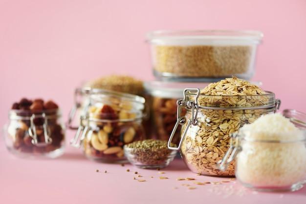 Alimento natural do vegetariano sobre o fundo cor-de-rosa com espaço da cópia. nozes, sementes, cereais, grãos em potes de vidro. Foto Premium