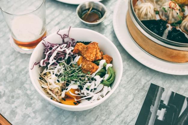 Alimento pan-asiático - somas não ofuscantes diferentes na bacia e na salada de bambu. almoço para dois com cerveja Foto Premium