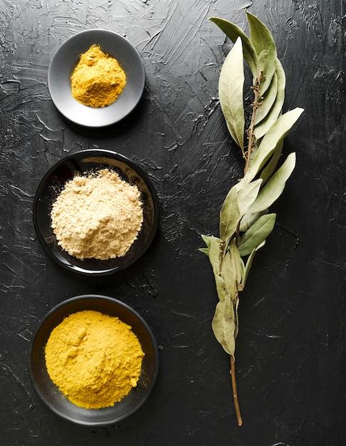 Alimentos em pó em tigelas e folhas de ingredientes Foto gratuita