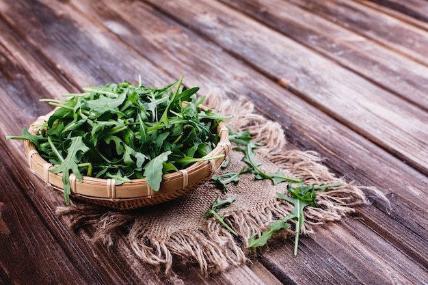 Alimentos frescos, vida saudável. rúcula verde servido na tigela sobre fundo rústico Foto gratuita