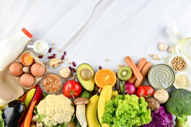 Alimentos saudáveis coloridos mistos no fundo da bancada da cozinha de mármore Foto Premium