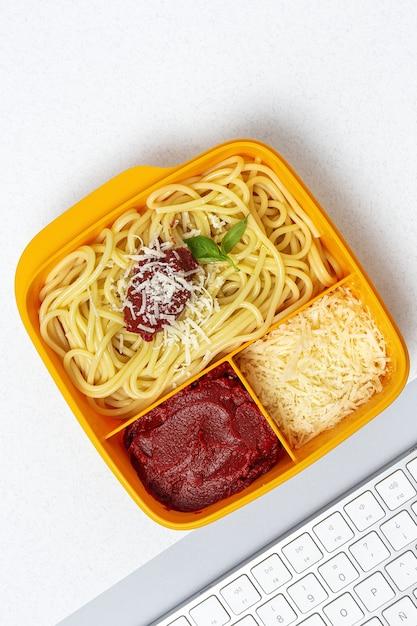 Alimentos saudáveis em recipientes plásticos prontos para comer com espaguete caseiro com tomate, queijo e manjericão na mesa de trabalho. comida italiana. para tirar. Foto Premium