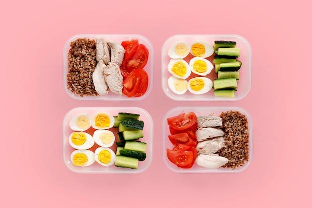 Alimentos saudáveis para o dia todo. várias porções em recipientes em fundo rosa Foto Premium