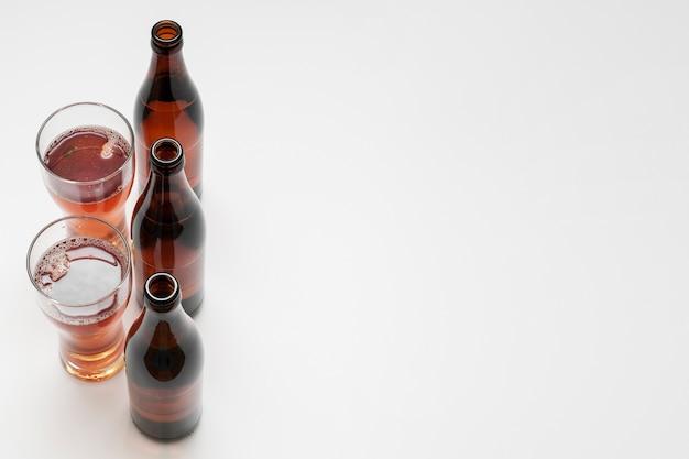 Alinhado garrafas de cerveja e copos em fundo branco, com espaço de cópia Foto gratuita