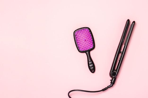 Alisador de cabelo e penteie em uma superfície rosa. conceito de cuidados com os cabelos, penteado, salão de beleza, cabeleireiro. vista plana, vista superior Foto Premium