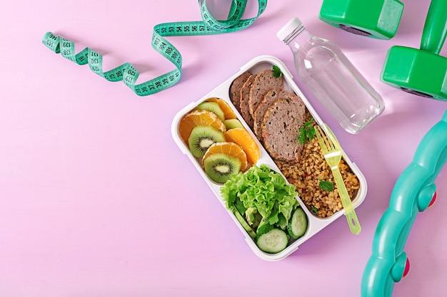 Almoço saudável com bulgur, carne e legumes frescos e frutas em um fundo rosa. Foto Premium