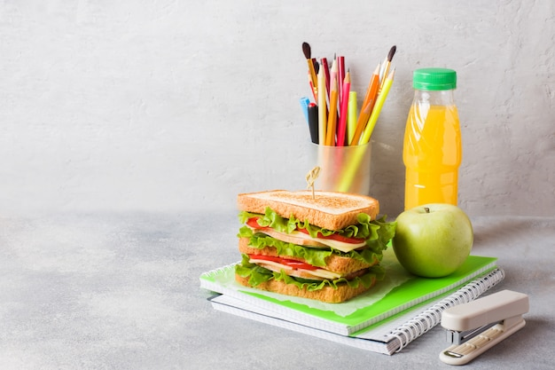 Almoço saudável para a escola com sanduíche, maçã fresca e suco de laranja. Foto Premium