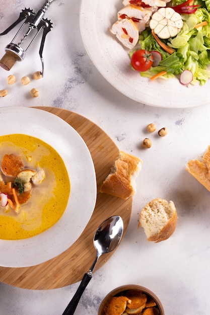 Almoço sopa de frango com croutons e salada de peito de frango e vinho sobre um fundo claro Foto Premium