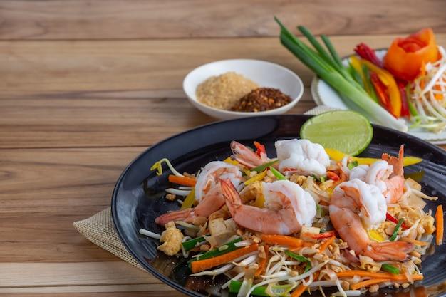 Almofada tailandesa, camarão fresco em um prato preto, colocado sobre uma mesa de madeira. Foto gratuita