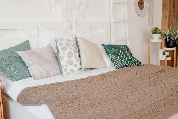 Almofada verde, bege na cama no quarto com lençóis de cor pastel na cama. design de apartamento elegante em estilo lagom. interior branco escandinavo elegante com cama, planta tropical, cobertor aconchegante. Foto Premium