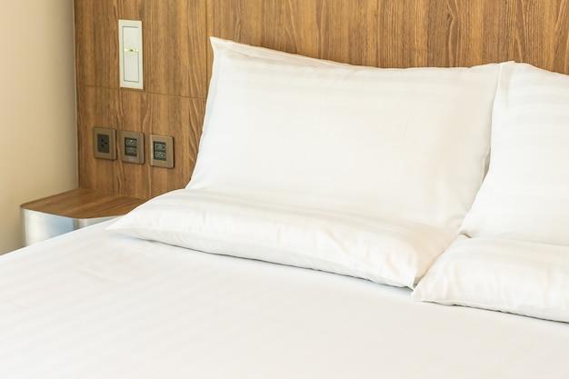 Almofadas brancas confortáveis na cama com cobertor Foto gratuita